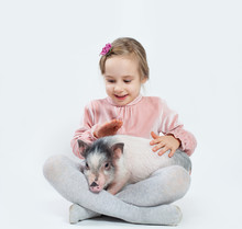 Happy Child Girl With Pig. Child And Pet