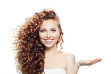 Cheerful Woman With Long Curly Hair, Clear Skin And Empty Open Hand Isolated On White Background