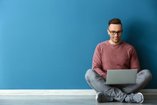 Young Man With Laptop Sitting Near Color Wall