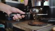 Hand crushing roasted berries beans with coffee grinder