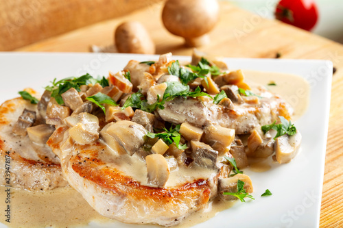 Two pork chops with sauce made from cream and mushrooms
