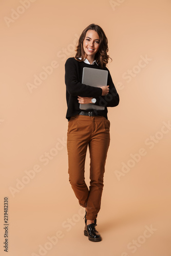 Photo of smiling woman 20s standing and holding laptop, isolated over beige background