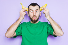Young Bearded Man Holding Cut In Half Yellow Banana On The Level Of Temples, Dumb And Silly Face Expression, Eyes Crossed. Light Purple Background, Copy Space.