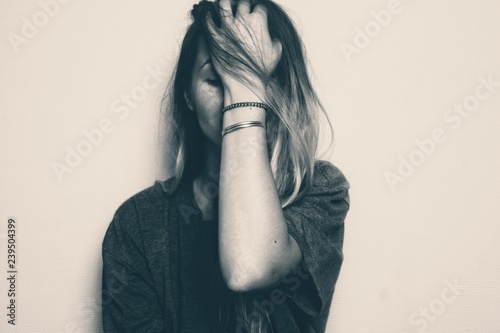 Fotografia Blonde girl covering her face with her left hand