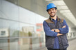 Smiling industrial worker in hardhat infront of modern building