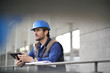 Handsome building expert in hardhat outdoors with tablet and blueprint