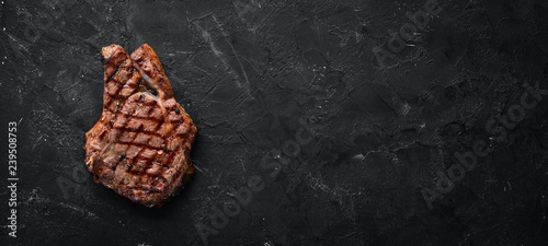 Veal steak on a bone on a black background. Free space for your text. Top view.