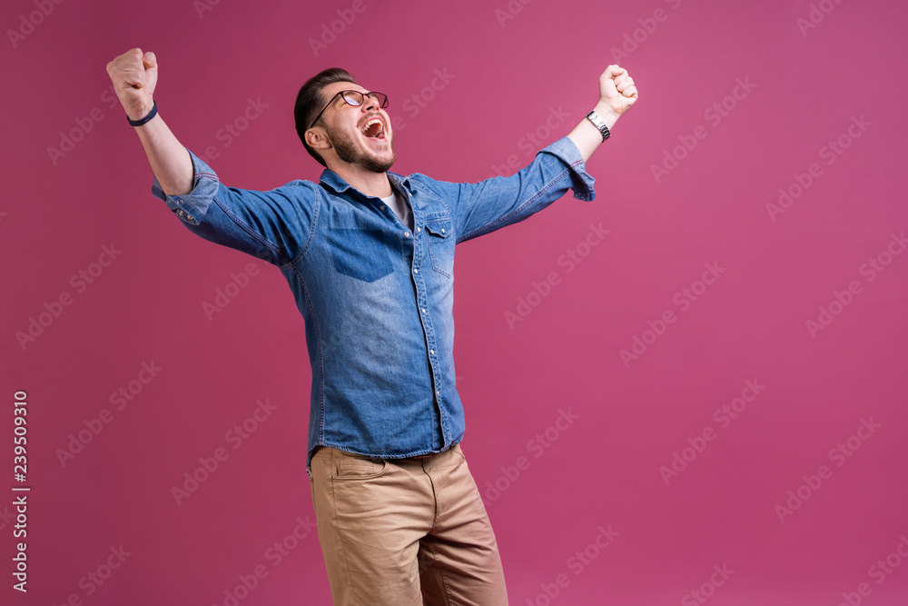 Fototapeta Portrait of a satisfied young man celebrating success isolated over pink background.