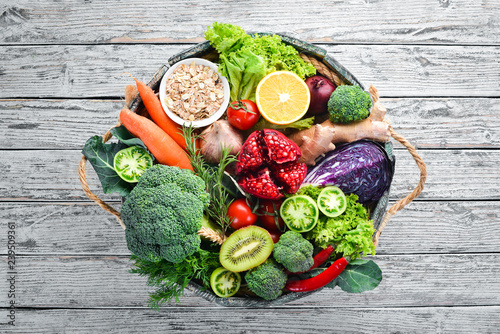 Valokuva  Fresh vegetables and fruits in a wooden box on a white wooden background