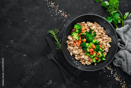 Garden Poster Personal A plate of healthy food. Oatmeal with broccoli, carrots and parsley. Top view. On a black background. Free copy space.
