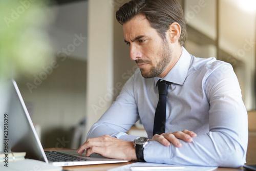 Fotografía  Handsome businessman working on laptop in modern office