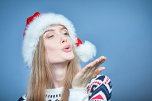 Woman Wearing Santa Hat Blowing At Open Hand Palm With Copy Space