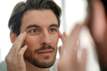 Handsome Man Checking Wrinkles In Mirror At Home