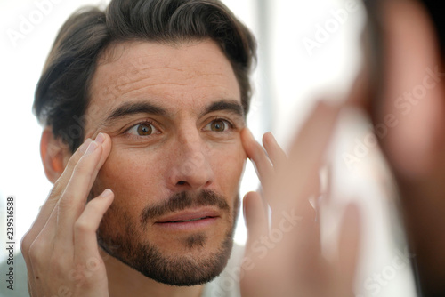 Tablou Canvas Handsome man checking wrinkles in mirror at home