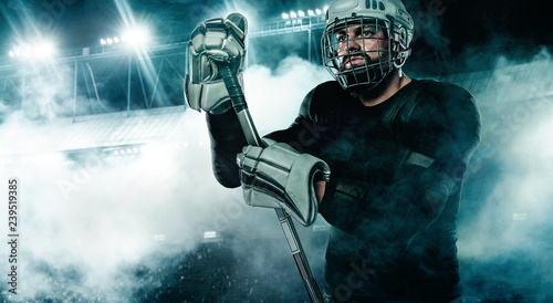 Ice Hockey player in the helmet and gloves on stadium with stick. Canvas Print