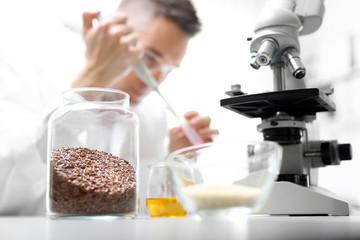 Laboratorium. Badanie żywności.  Laborant w pracowni laboratorium naukowego analizuje pod mikroskopem.