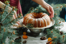 Gingerbread Bundt Cake For Christmas With Orange Glaze And Spruce Branches Over Dark Background. Women Is Icing Bundt Cake. Christmas Table.