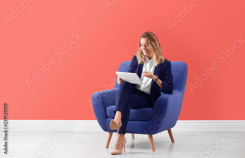Photo  Young woman with tablet sitting in armchair indoors