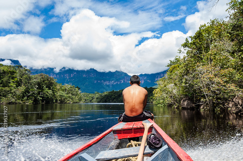 Photo close up view from behind of young bare chested indigenous man with riding woode
