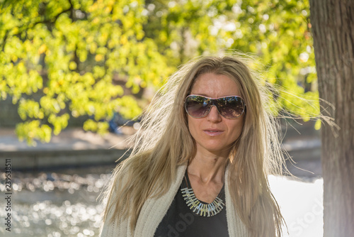 Fotografie, Obraz  Attractive blonde young woman in a park with blurred background