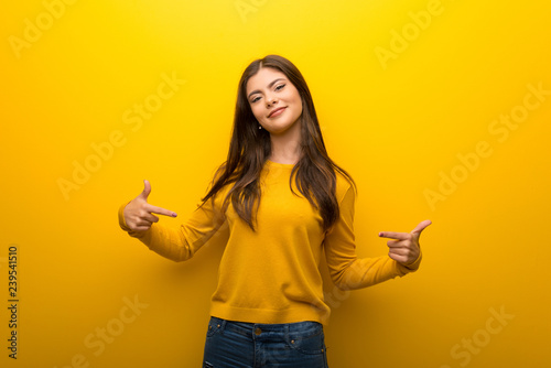 Foto  Teenager girl on vibrant yellow background proud and self-satisfied in love your