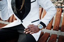 Chic Handsome African American Man In White Suit Sitting On Bench. Close Up Photo Of Golden Watches On Hand.
