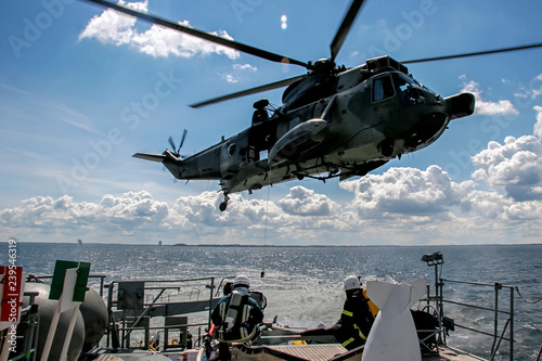 NATO rescue mission in sea with ship and helicopter. Wallpaper Mural