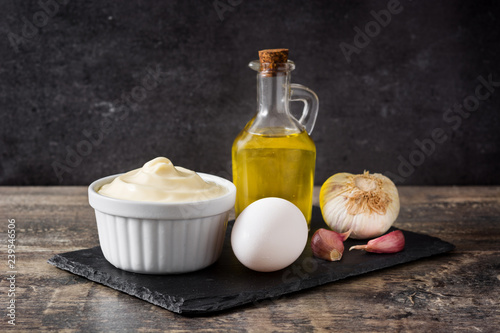 Photo Aioli sauce and ingredients on wooden table