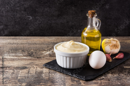 Aioli sauce and ingredients on wooden table. Copyspace Canvas Print