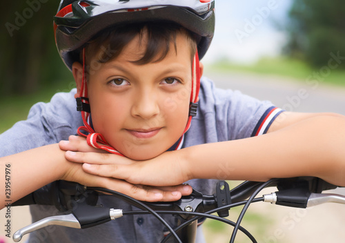 Fotografie, Obraz  Close-up of a teenager boy in protective helmet sitting on his bicycle and keeps his head on his hands resting on the handlebars of the bike in park on summer day