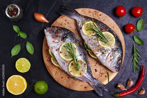 Fotografie, Obraz  Sea bream or dorado  fish with lemon, herbs, vegetables and spices