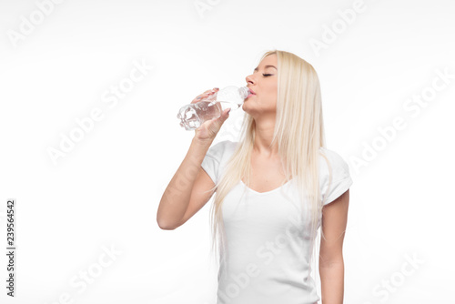 Fotografía  Healthy blond woman holding and drink glass of pure water on isolated white back