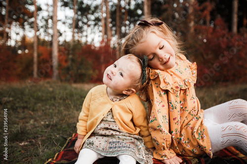 Foto auf AluDibond Schokobraun Young children walk in the autumn forest in retro dresses.