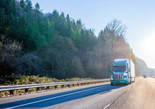 Green Classic American Modern Big Rig Semi Truck Transporting Cargo In Refrigerated Semi Trailer Running On Wide Highway In Sunshine And Trees On Roadside