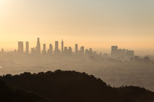 Hazy Orange Dawn Cityscape View Of Downtown Los Angeles, Hollywood With Runyon Canyon Park Hilltop In Foreground.