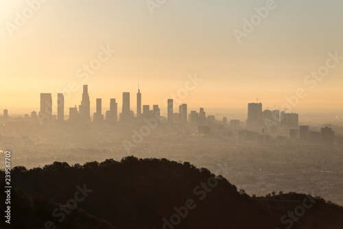 Valokuvatapetti Hazy orange dawn cityscape view of downtown Los Angeles, Hollywood with Runyon Canyon Park hilltop in foreground