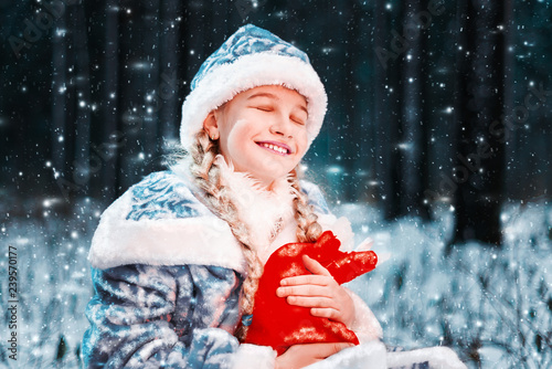c5ce6b644 beautiful portrait of the snow maiden in a festive costume. happy little  girl is holding new year bag with gifts. fabulous winter forest. Merry  Cristmas.