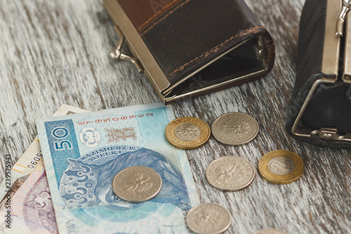 Fotografía  Polish zloty with little wallets on the old wooden background
