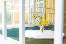 Yellow-pink Bouquet Of Wild Flowers On The Table. Photo In Bright Colors. Table And Bouquet Can Be Seen Through The Window Of The Balcony Or Veranda.
