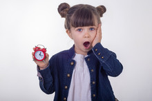 Omg, Wake Up! Surprised Girl In Dress With Red Clock On White Background. Shocked Kid Holding Alarm Clock. Time Range Or Deadline Concept.