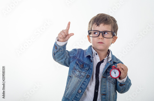 Fotografía  Happy young boy in white t-shirt and jeans jacket thinking and looking up with red clock pointing finger up on white background