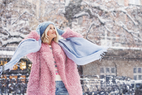 Outdoor portrait of young beautiful fashionable happy smiling girl wearing trendy pink faux fur winter coat, light blue beanie hat, scarf, posing in snow covered street. Copy, empty space for text