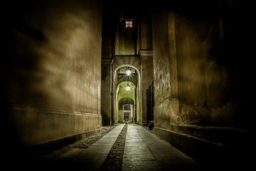 ciemna wąska uliczka oświetlona mdłym światłem