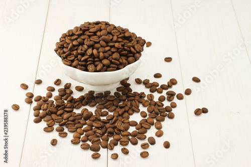Fotografie, Obraz  Roasted coffee beans in bowl on white wooden background
