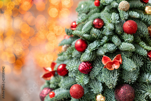Beautiful small decorated Christmas tree on dark wooden table. Happy mood. Garland bokeh on background. Wallpaper. Danish pine and fir, Nobilis