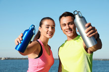 Young Sporty Couple With Water Bottles Near River On Sunny Day