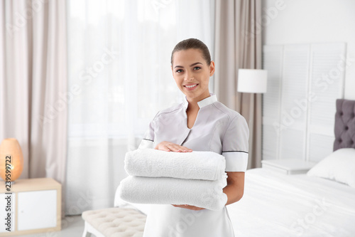 Young chambermaid with clean towels in bedroom