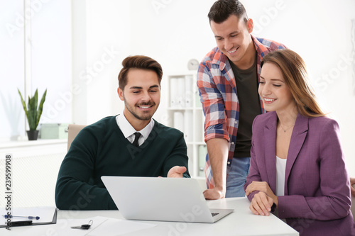 Real estate agent consulting young couple in office Wallpaper Mural