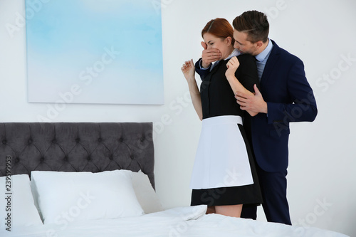 Fototapeta Man molesting chambermaid in bedroom. Sexual harassment at work obraz