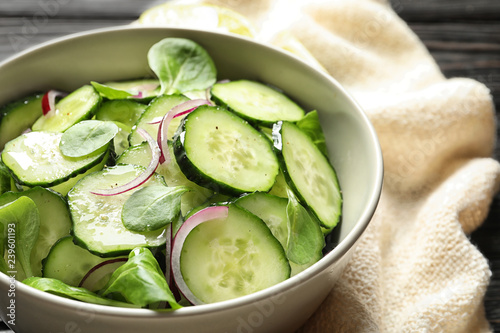 Delicious cucumber salad with onion and spinach in bowl on table, closeup